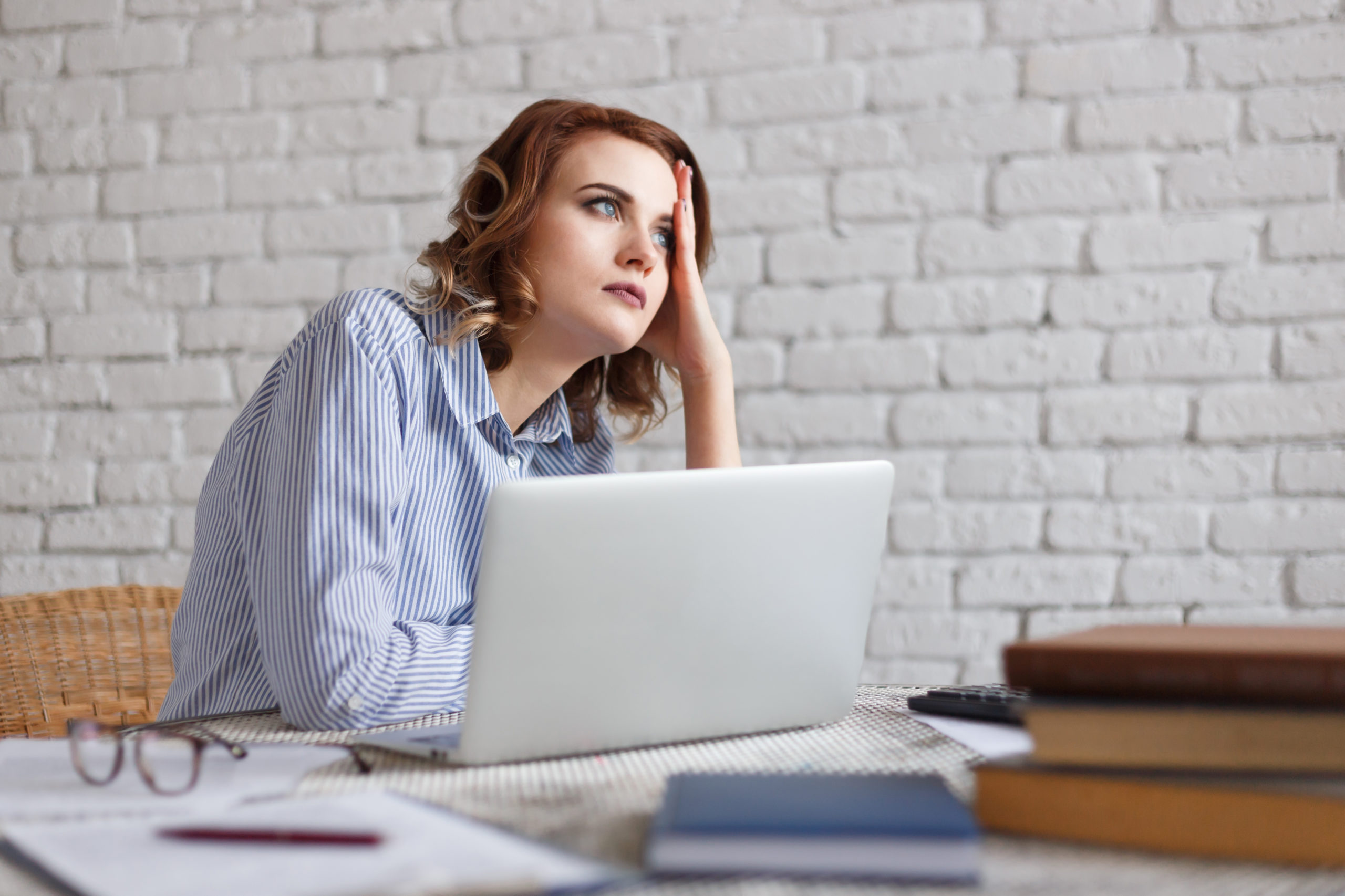 woman thinking of social media content in front of a laptop